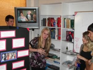 at the Alliance Française de Sacramento of a student explaining her exhibit to a guest