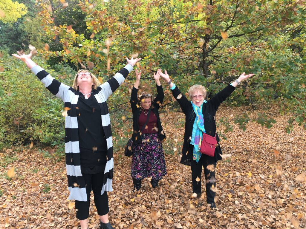 Anne Kenneally throwing leaves with Cynthia and Barbara